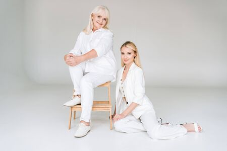 full length view of smiling blonde grandmother sitting on chair near beautiful granddaughter in total white clothes