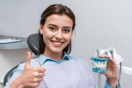 happy woman holding teeth model and showing thumb up in dental clinic 写真素材