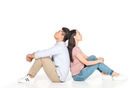 young asian couple sitting back to back with closed eyes on white background
