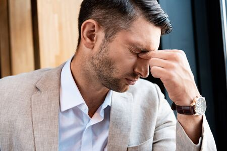 tired businessman touching nose with closed eyes in cafe