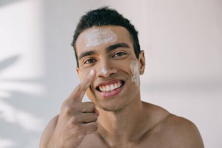 handsome mixed race man applying cosmetic cream on face with finger and smiling while looking away