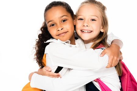 two happy multicultural schoolgirls hugging while smiling at camera isolated on white 写真素材 - 131988278