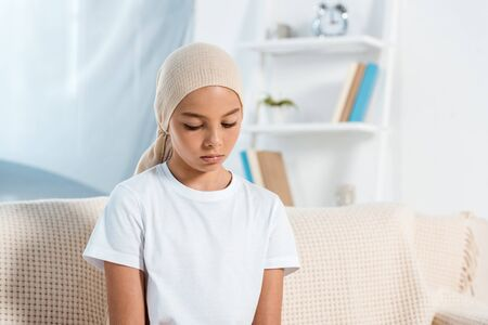 frustrated kid in head scarf sitting on sofa in living room