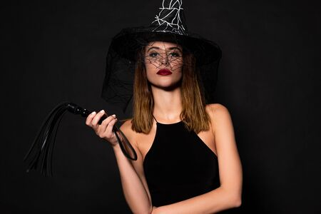 attractive woman in witch hat holding flogging whip isolated on black Stock Photo