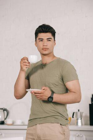 homme asiatique pensif buvant du café tout en se tenant dans la cuisine et en détournant les yeux Banque d'images