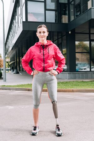 full length view of smiling disabled sportswoman standing with hands on hips on street