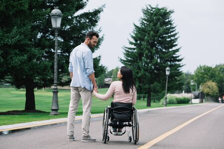 back view of young disabled woman holding hands with handsome boyfriend while walking in park together