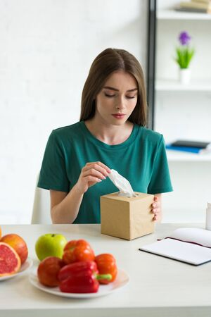 girl with allergy holding napkins while sitting at table with fruits and vegetables Archivio Fotografico