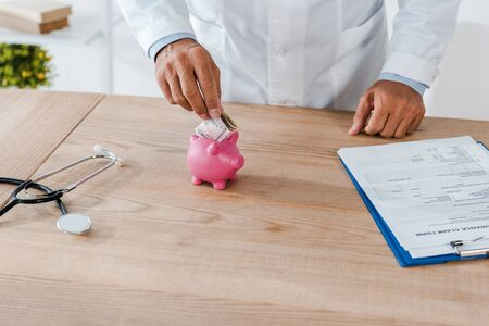 cropped view of man in white coat putting dollar banknote in piggy bank near clipboard and stethoscope Banque d'images - 131821644