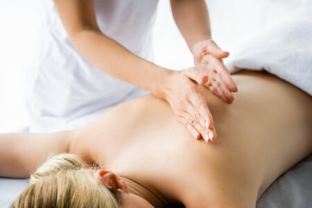 cropped view of masseur doing back massage to woman in spa
