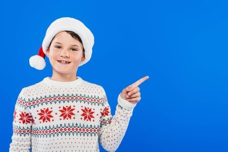 front view of smiling kid in santa hat pointing with finger isolated on blue