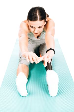 low angle view of disabled sportswoman stretching on fitness mat isolated on white