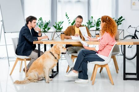 three friends sitting at table and doing paperwork in office Фото со стока
