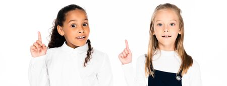 panoramic shot of two cute multicultural schoolgirls looking at camera and showing idea gestures isolated on white 写真素材 - 131989411