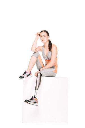 disabled sportswoman with prosthetic leg sitting isolated on white