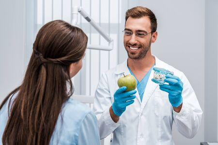selective focus of happy dentist in glasses holding tooth model near patient