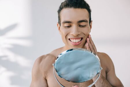 handsome mixed race man touching face with hand while smiling and looking at mirror
