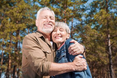 smiling senior couple of tourists embracing with closed eyes in sunny day 版權商用圖片