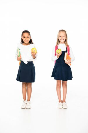 full length view of two smiling multicultural schoolgirls holding books and apples on white background 写真素材 - 131990798