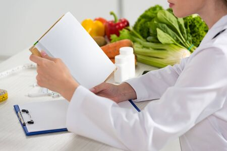 cropped view of dietitian in white coat reading book at workplace Stock fotó