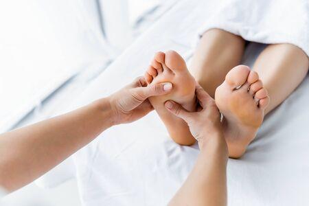 Vista recortada del masajista haciendo masaje de pies a la mujer en el spa Foto de archivo