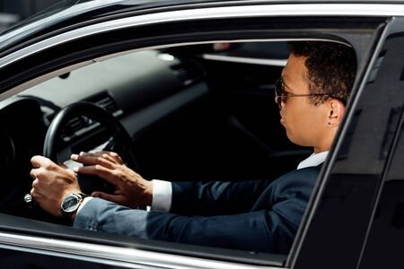 african american businessman in suit and sunglasses beeping in car at sunny day Stock Photo