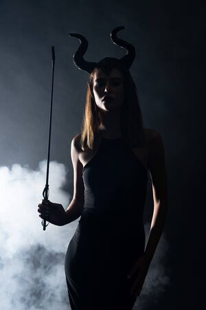 silhouette of young woman with horns holding flogging whip on black with smoke 写真素材