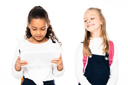 cheerful schoolgirl looking at african american friend using digital tablet isolated on white 写真素材
