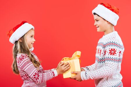two smiling kids in santa hats with present looking at each other isolated on red