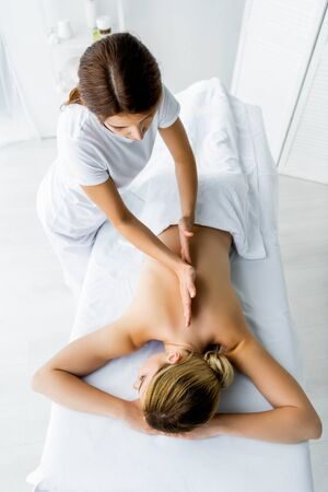 high angle view of masseur doing back massage to woman in spa  Stok Fotoğraf