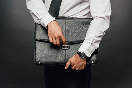 cropped view of african american businessman holding leather briefcase on dark background 版權商用圖片