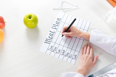 cropped view of dietitian writing in meal plan at table with fruits Stockfoto