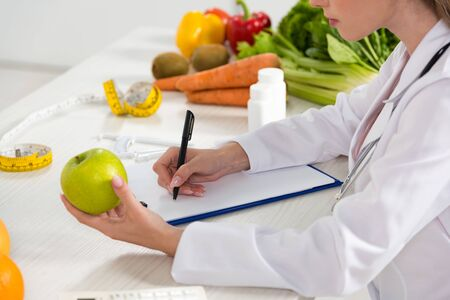 cropped view of dietitian in white coat holding green apple and writing in clipboard