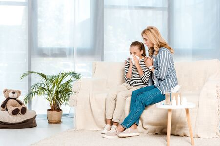 mother sitting with ill daughter sneezing in tissue at home