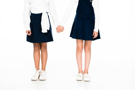 cropped view of two multicultural schoolgirls holding hads on white background 写真素材 - 131992547