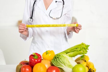 cropped view of dietitian in white coat holding measure tape near fresh fruits and vegetables Zdjęcie Seryjne