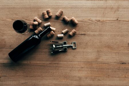 top view of bottle of wine, wine glass, corks and corkscrew on wooden surface