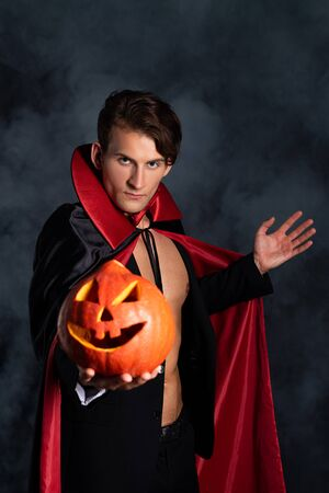 Gut aussehender Mann, der Halloween-Kürbis hält und auf Schwarz mit Rauch gestikuliert