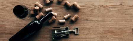 panoramic shot of bottle of wine, wine glass, corkscrew and corks on wooden surface