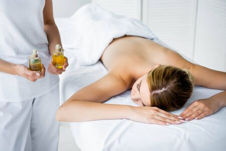cropped view of masseur holding fragrance oils and woman lying on massage mat  Stok Fotoğraf