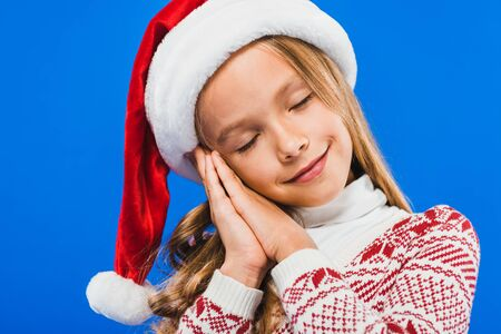 cute kid in santa hat and sweater sleeping isolated on blue