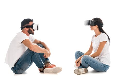 side view of happy man with crossed legs sitting while using virtual reality headset near woman on white 免版税图像
