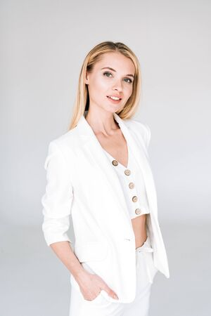 beautiful young blonde woman in total white outfit with hands in pockets isolated on grey Reklamní fotografie