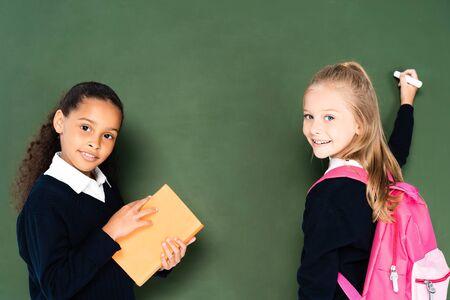 african american schoolgirl holding book near classmate with piece of chalk near green chalkboard 写真素材 - 132004035