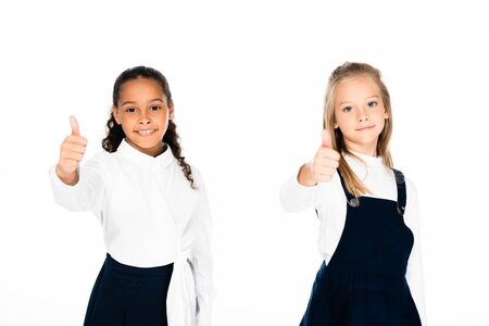 two smiling multicultural schoolgirls showing thumbs up while looking at camera isolated on white