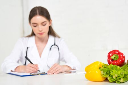 selective focus of dietitian in white coat writing in clipboard