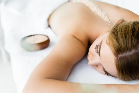 selective focus of woman lying on massage mat with sea salt on back