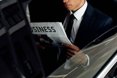 cropped view of african american businessman reading business newspaper in car