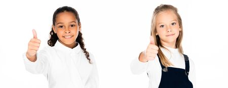 panoramic shot of two multicultural schoolgirls showing thumb up while looking at camera isolated on white 写真素材 - 132004385