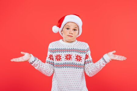 front view of child in sweater and santa hat showing shrug gesture isolated on red Stock Photo